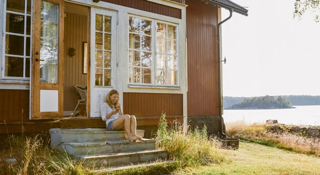 Woman using phone while sitting on steps in doorway of log cabin
